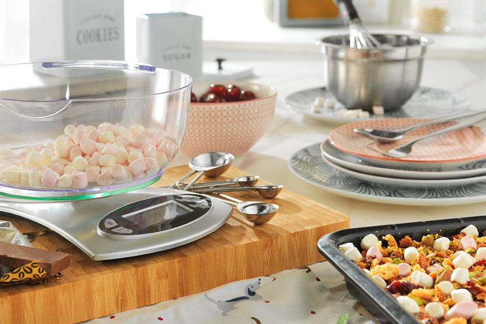 An image of a worktop where someone is baking rocky road. There's a scale, measuring cups and bowls plus marshmallows, cherries and chocolate.