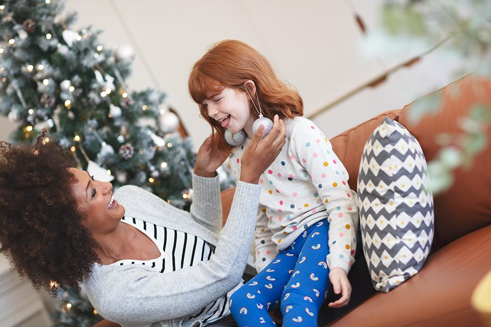 Image of a woman and girl sitting on a sofa in front of a Christmas tree. The woman is playfully hanging baubles from the ears of the girl as though they were earrings.
