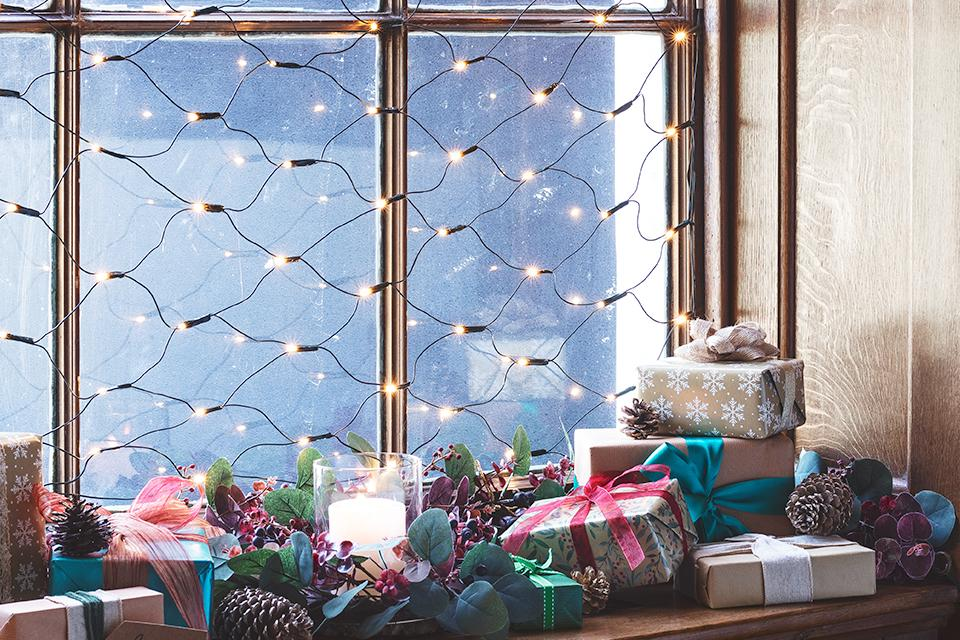 An image of net lights hung from the inside of a large window. There are presents on the window sill.