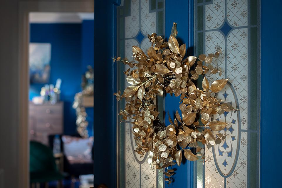 Gold leafed wreath on a blue door.