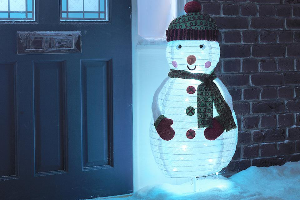 An image of a front door and the wall of a house. Sitting in front of the wall is a metre-tall snowman light decoration.