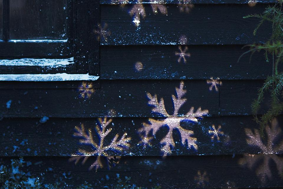 An image of the side of a wooden shed at night time. Projected onto the shed are large and small snowflakes, from a light projector.