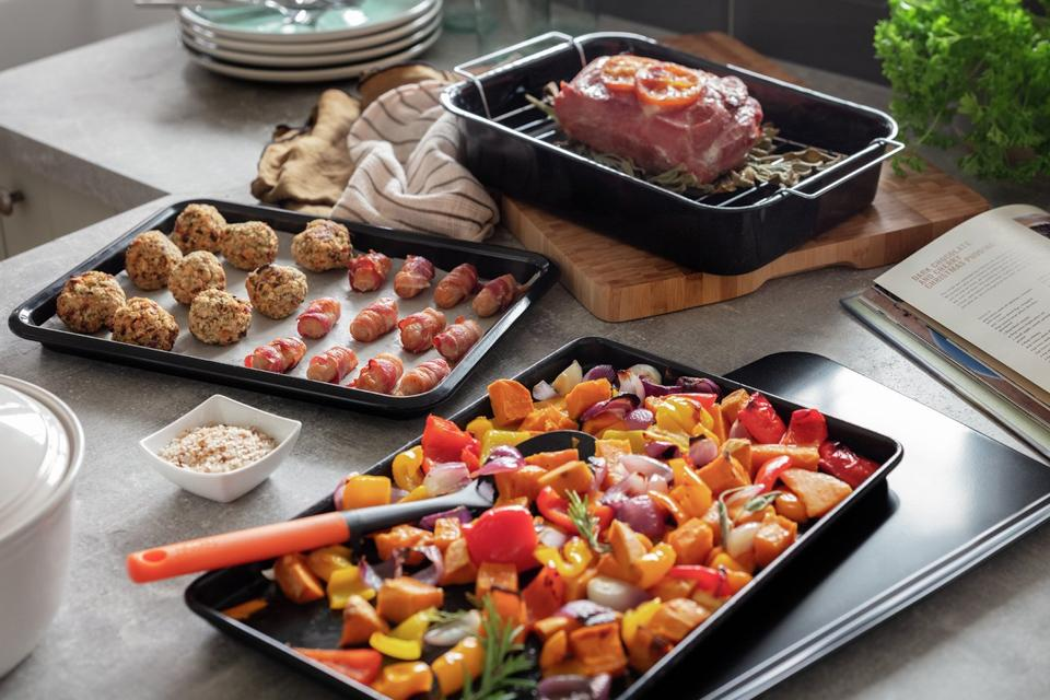Trays of roasted vegetables and pork and stuffing.
