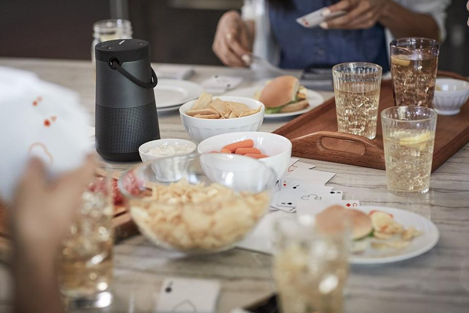 Speaker on table with drinks and snacks