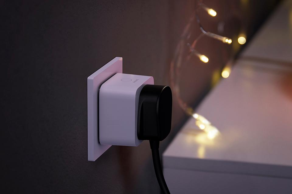 A Philips Hue smart plug with fairy lights in the background.