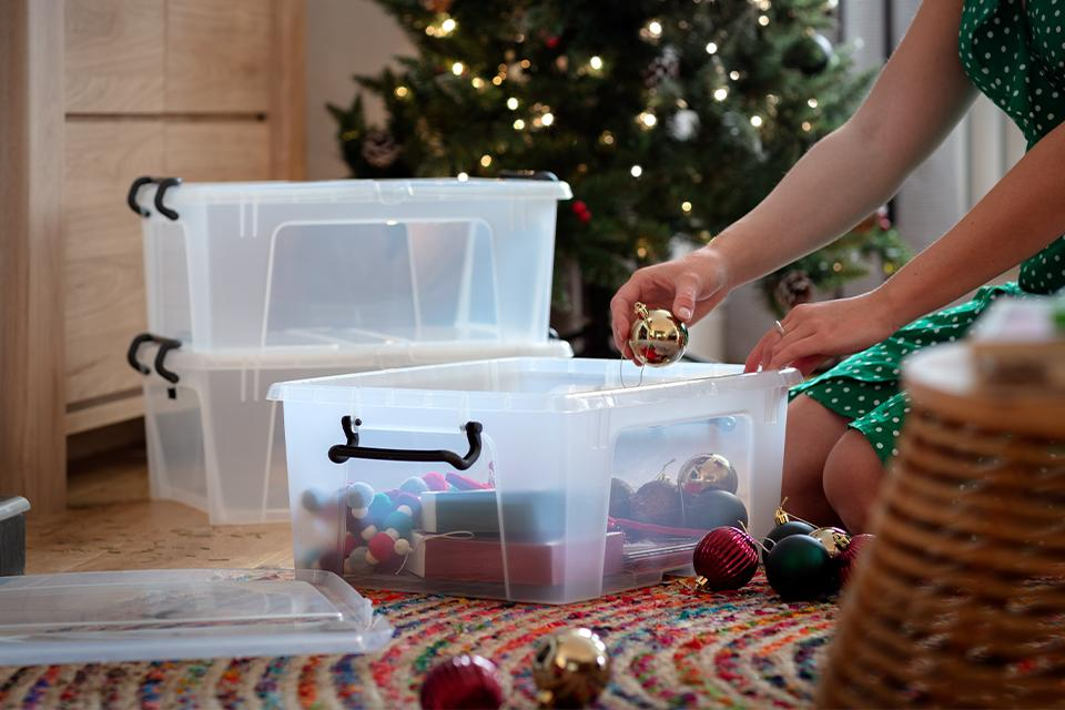 A woman stores Christmas baubles away in a plastic storage box.