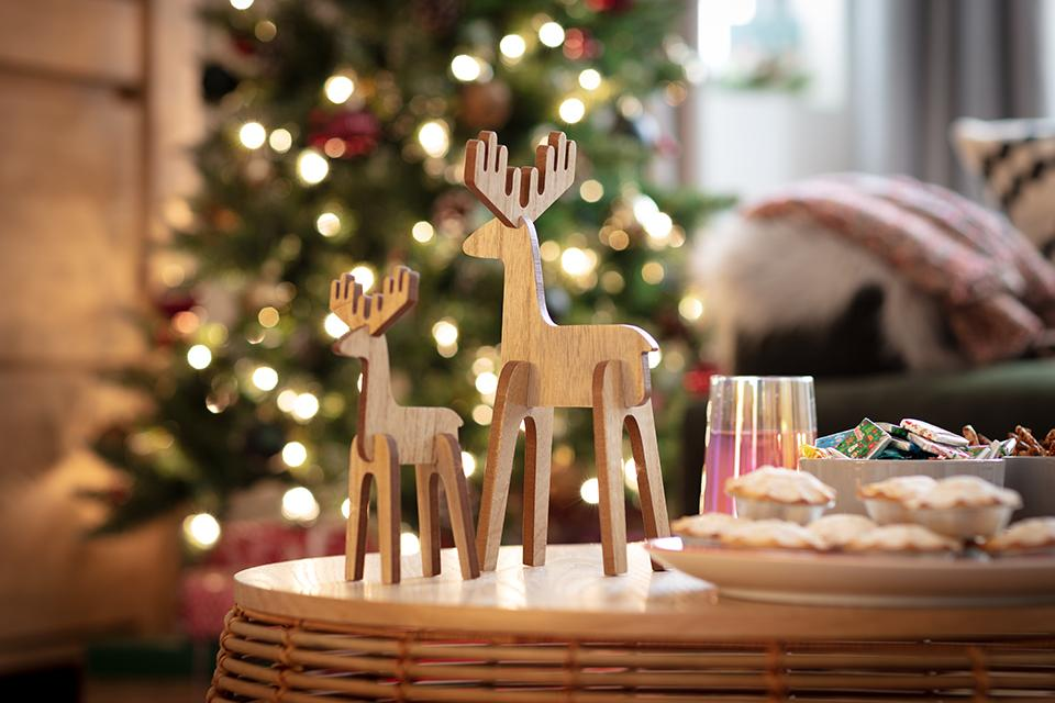 Two light wooden reindeer ornaments sat next to mince pies with a Christmas tree in the background.