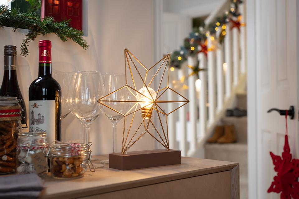 A gold star-shaped table lamp sat next to some Christmas treats and wine glasses.