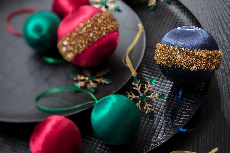Some fabric baubles in rich green, pink and blue tones with gold glitter.