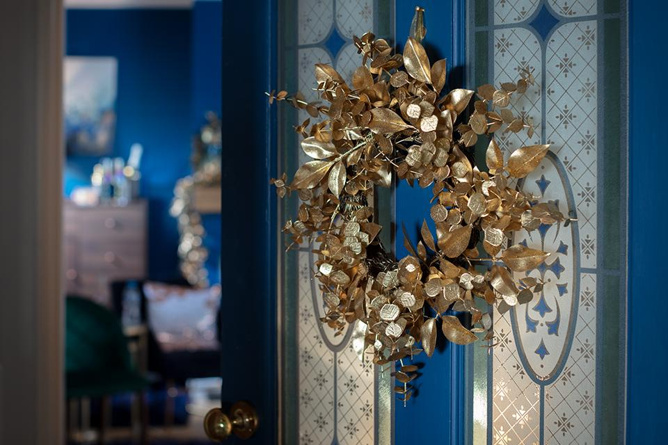 A gold foliage Christmas wreath on a blue front door.