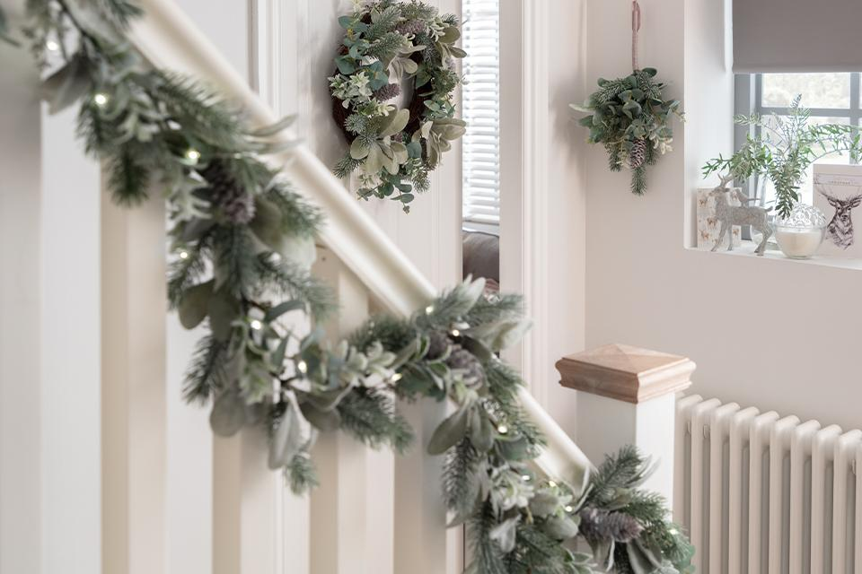 A frosted green foliage garland running down a banister, with matching wreaths on the wall.