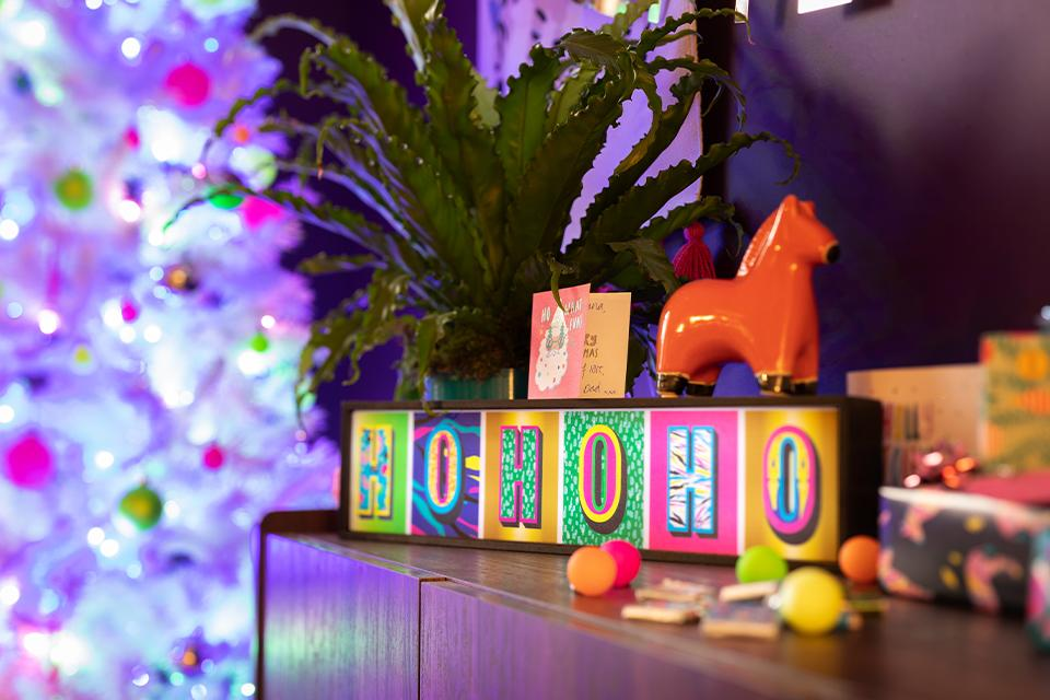 "A brightly coloured lit-up sign reading ""Ho Ho Ho"" on a dresser with a bright Christmas tree behind it."