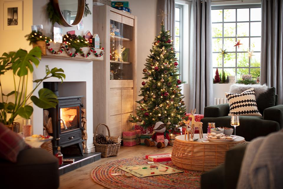 A cosy living room with a lit fire, Christmas tree with red baubles and Christmas decorations.