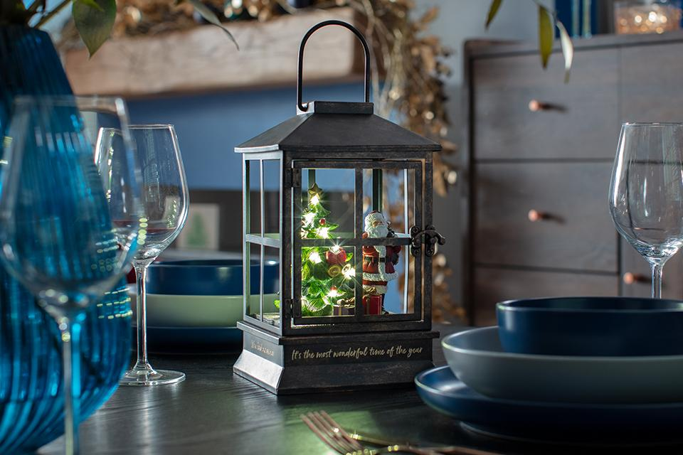 A grey lantern with a lit-up Christmas tree and Father Christmas inside, sat on a dining room table.