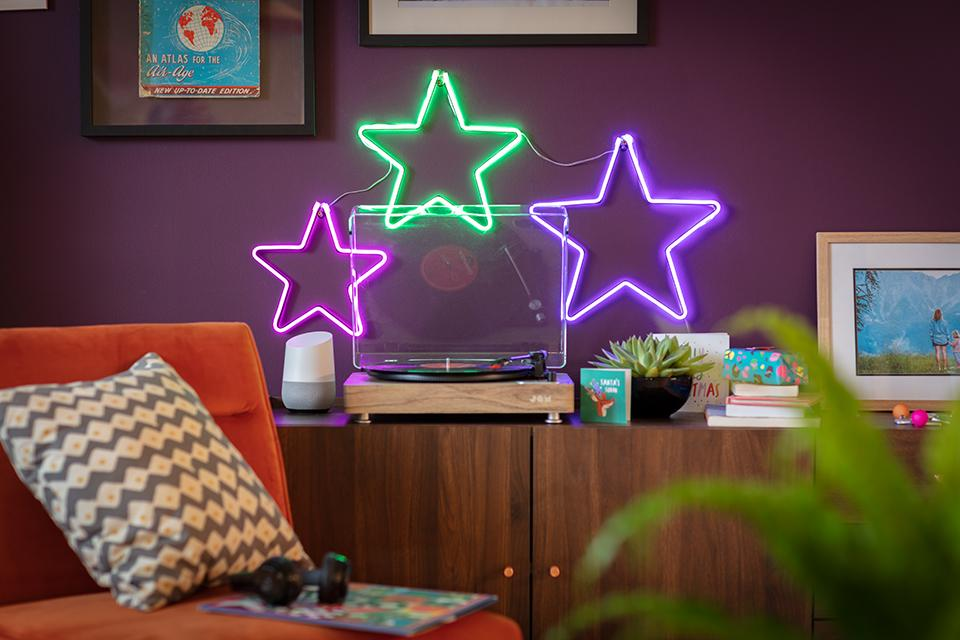 Three lit-up neon stars in pink, green and purple lit up on a wall behind a record player.