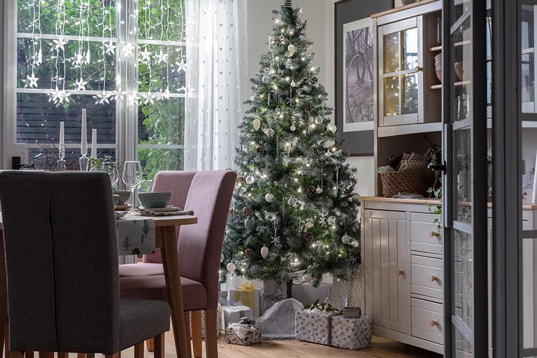 A Christmas tree decorated with white and silver baubles in a dining room.