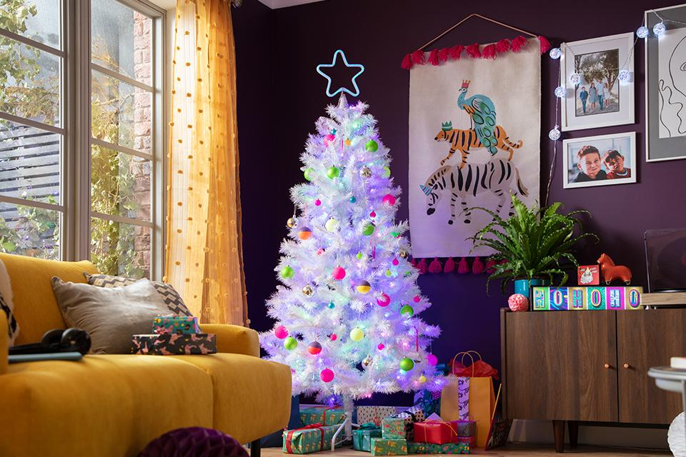 A bright white Christmas tree with pink, yellow and green baubles and a neon star topper.