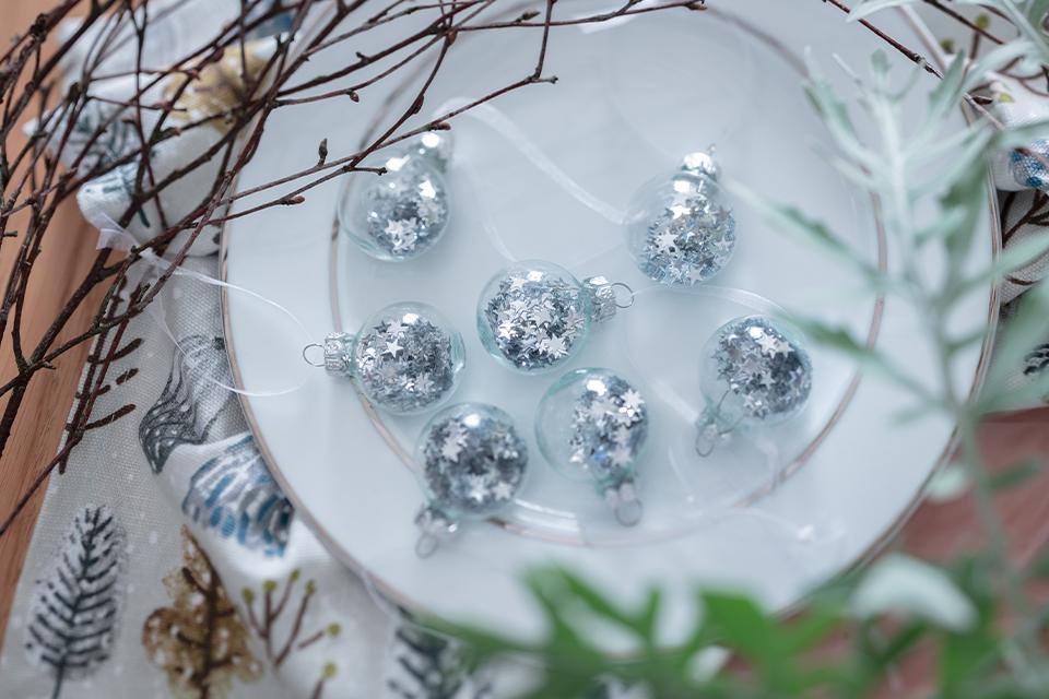 Clear baubles with loose sparkly silver stars inside placed on a white dinner plate.