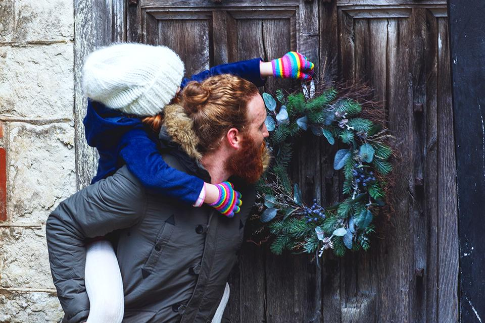 A father and daughter hang a wreath outside.