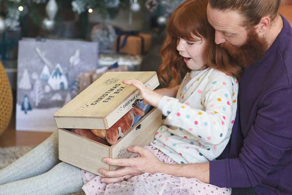 Young girl opening a Christmas Eve box filled with gifts.