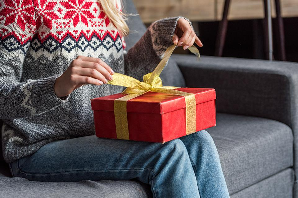 Woman in Christmas jumper opening present at home.