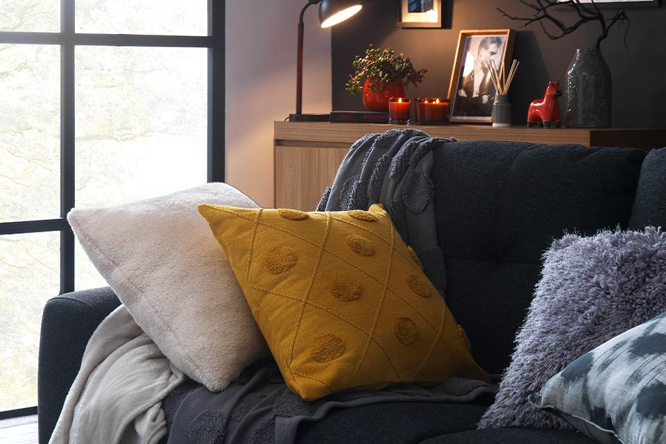 A comfy sofa topped with inviting cushions and throws.
