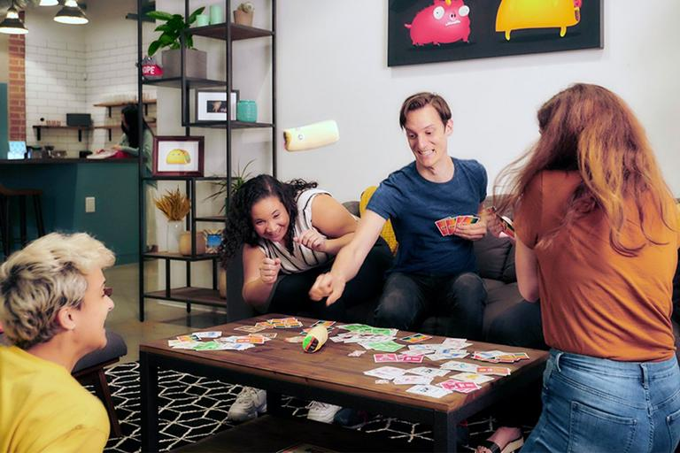 Four friends play a game in their living room.