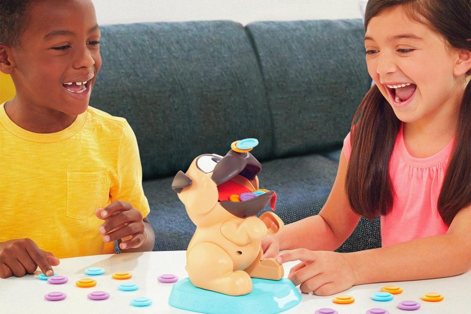 Two kids laugh while playing with a toy pub game.
