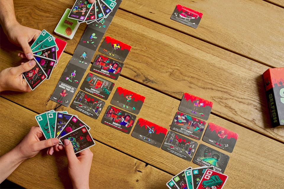 Four people play a card-based game.