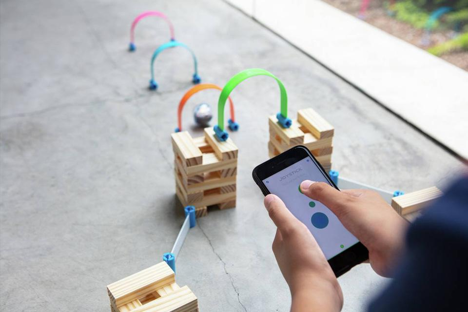 A Sphero ball navigates its way through some wooden blocks and obstacles.