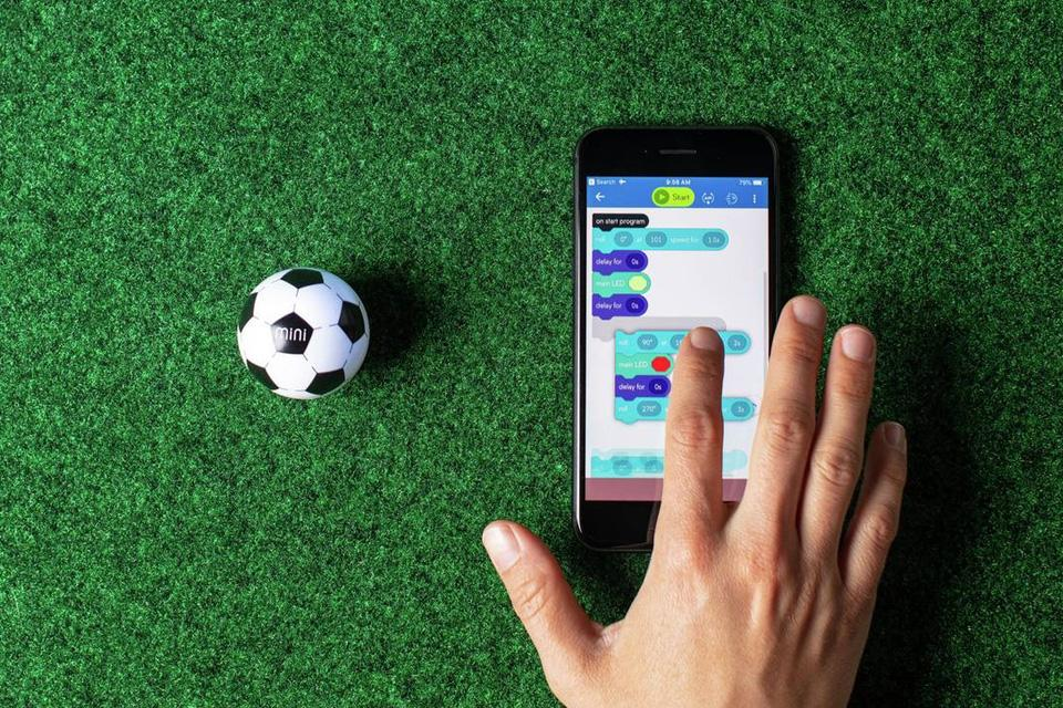 A hand on a smartphone coding instructions to a football Sphero.