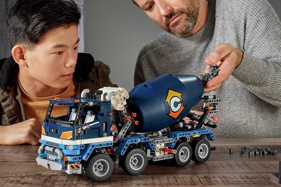 A boy and a man look with interest at a LEGO cement truck.