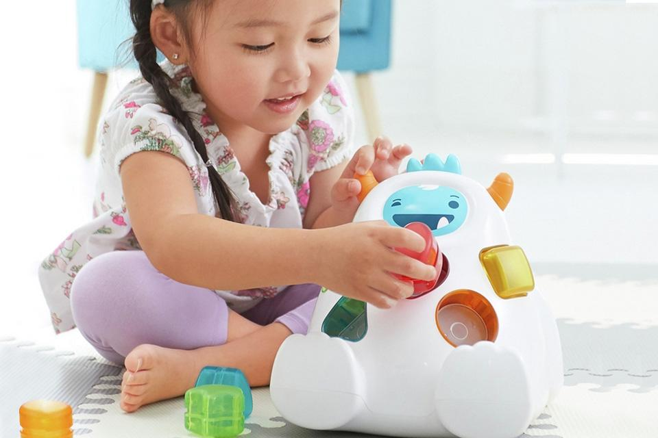 A toddler places colourful shapes into a shape sorting yeti toy.