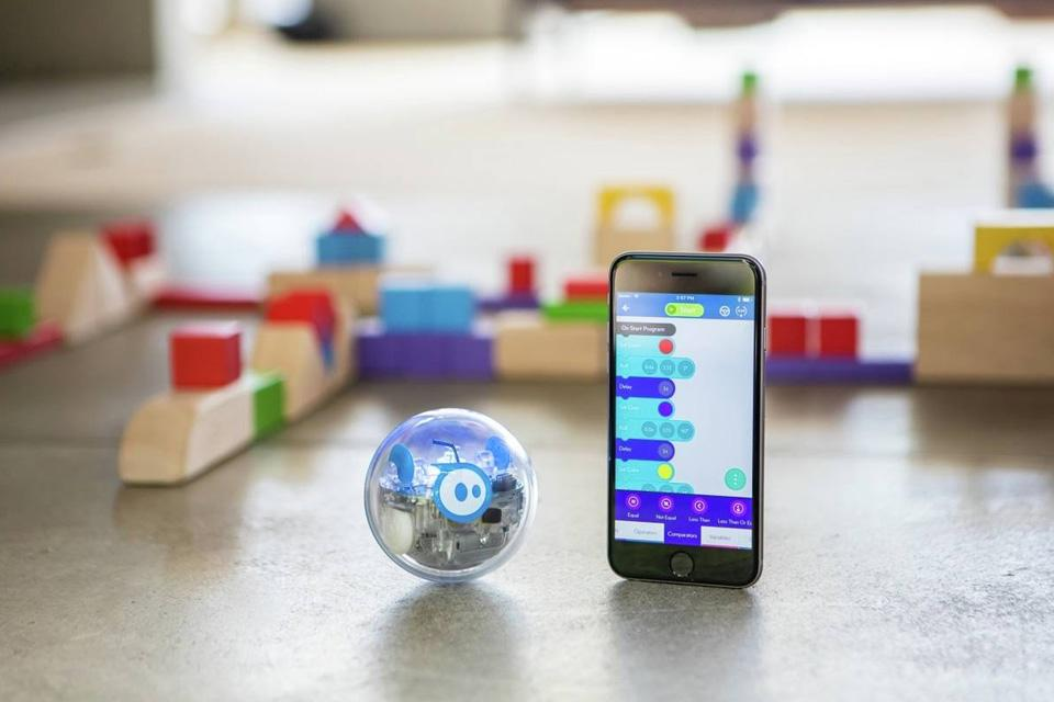 A Sphero codable robot next to a smartphone showing a coding app.