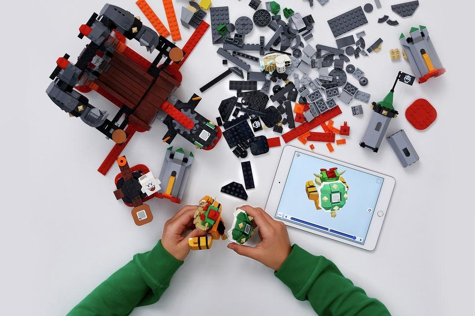 An overhead image of spread out LEGO, with an instruction manual shown on a tablet.