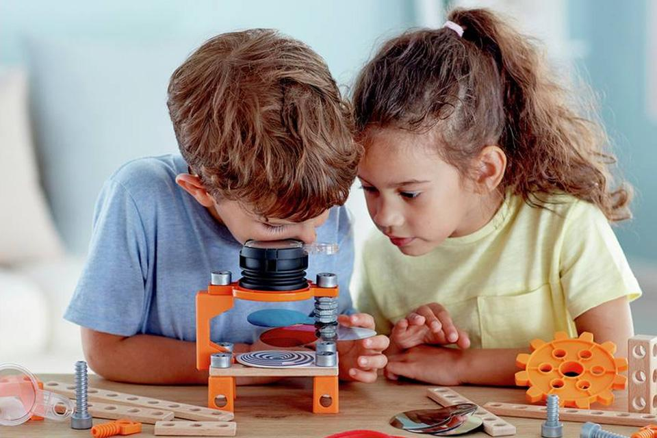 A boy and girl taking turns to view an optical illusion kit.