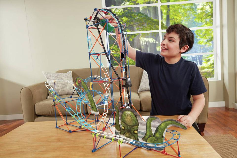 A boy admiring his completed K'NEX roller coaster.