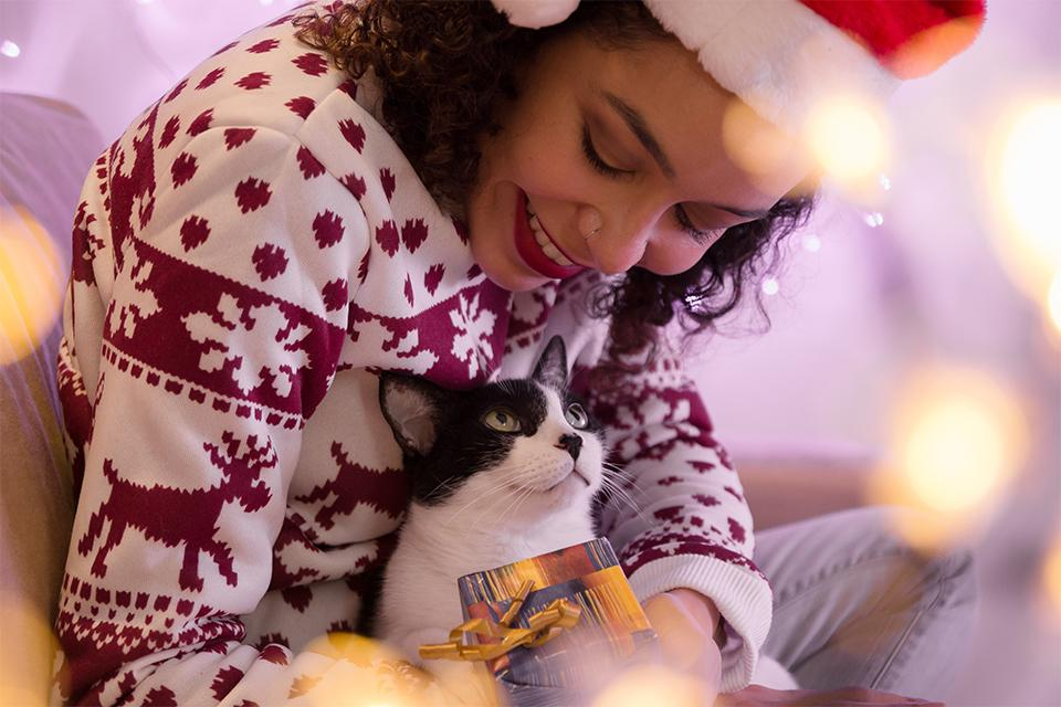 Woman in Christmas jumper cuddling black and white cat and holding a Christmas gift.
