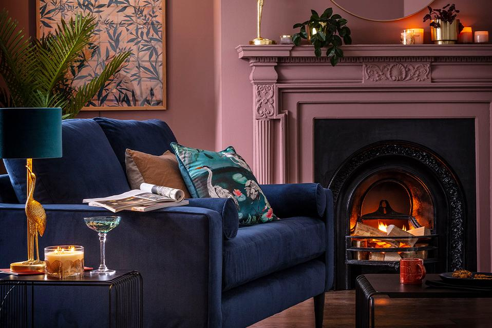 A cosy pink living room with fireplace and blue sofa.