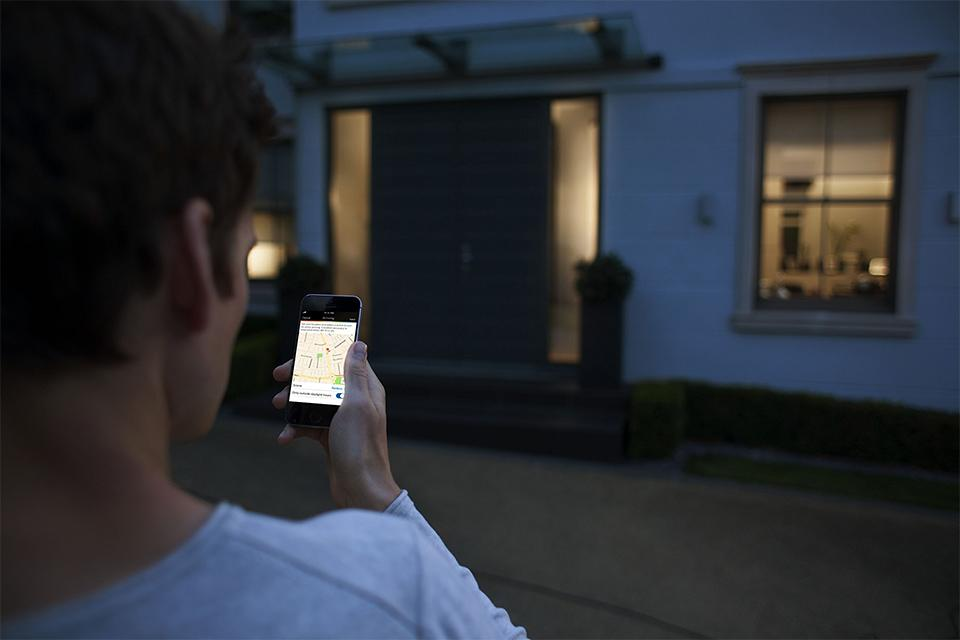 A man controls his home lighting from his smartphone.