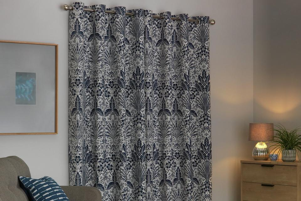 An image of some blue and white patterned curtains drawn in a lounge.