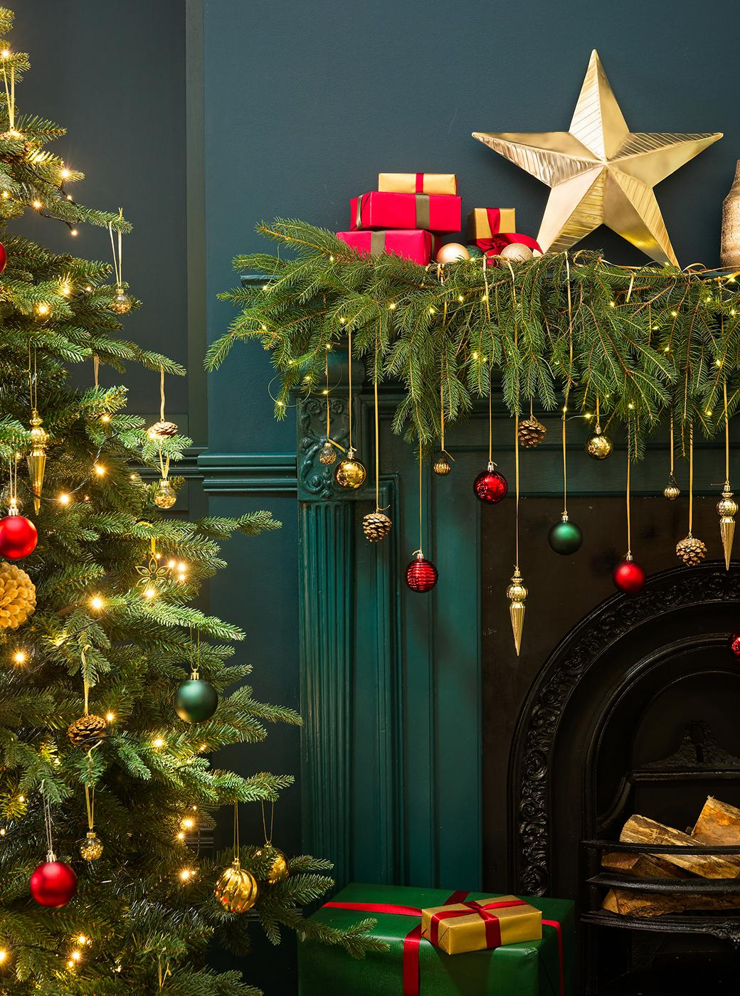 Christmas foliage on a mantelpiece with bauble decorations.