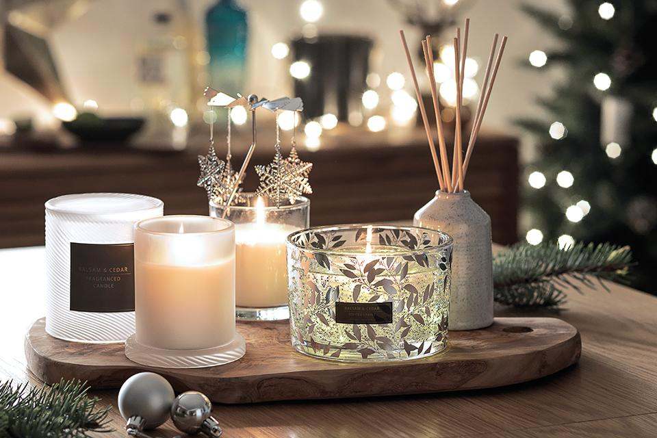 Christmas candles and home fragrance on wooden board.