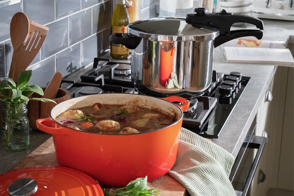 An image of a kitchen worktop. There's an orange casserole dish filled with a hearty stew next to a pressure cooker on the hob.