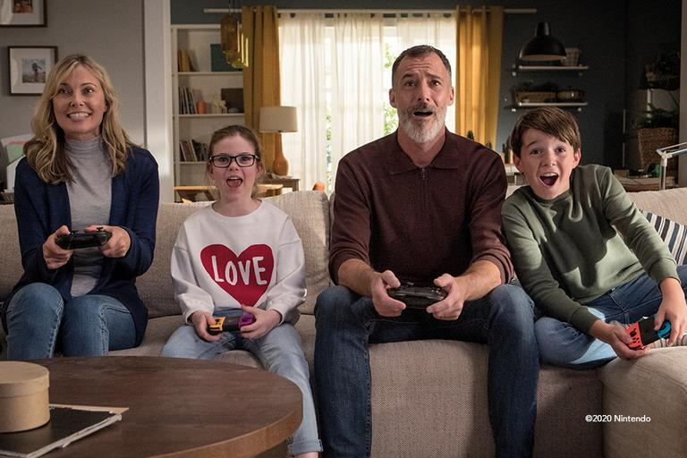 A family of four, playing the Nintendo Switch.