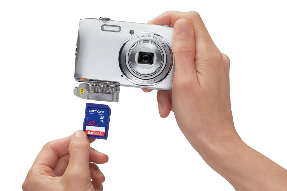 Close up of person's hands holding a camera in right hand and inserting a memory card into it with the left hand.