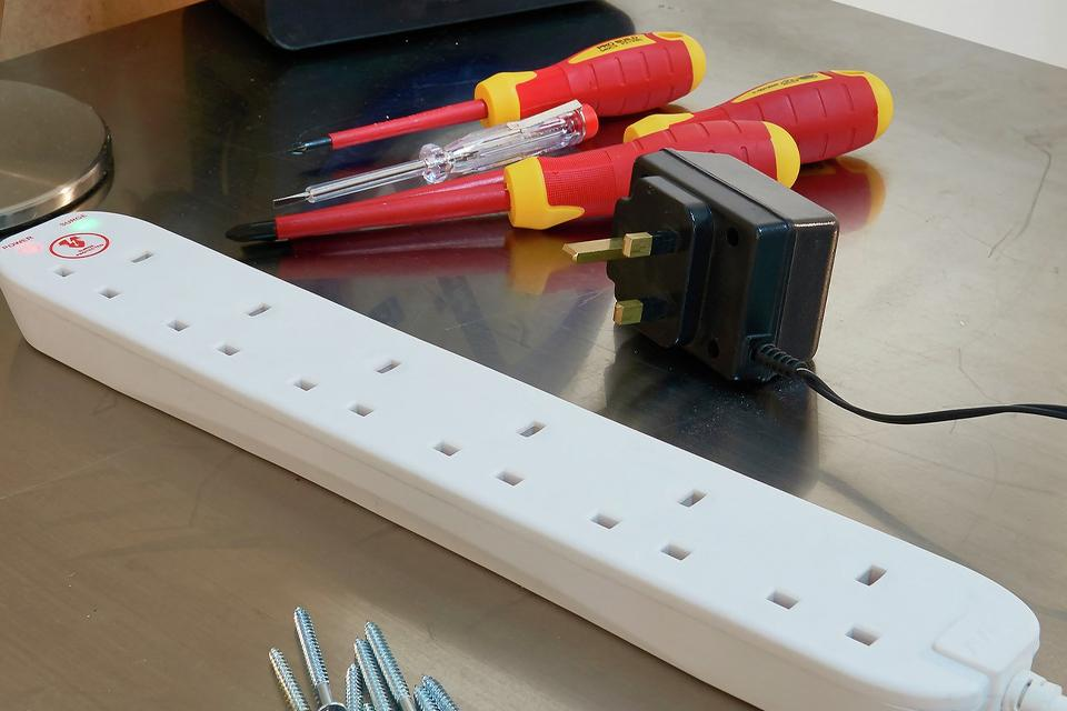 White extension lead on workbench with DIY tools and accessories around it.