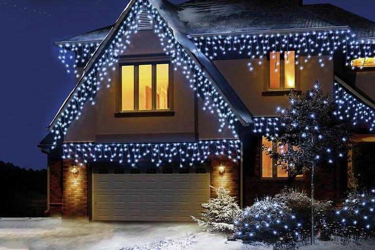 Icicle lights adorning the front fascia of a house at night.
