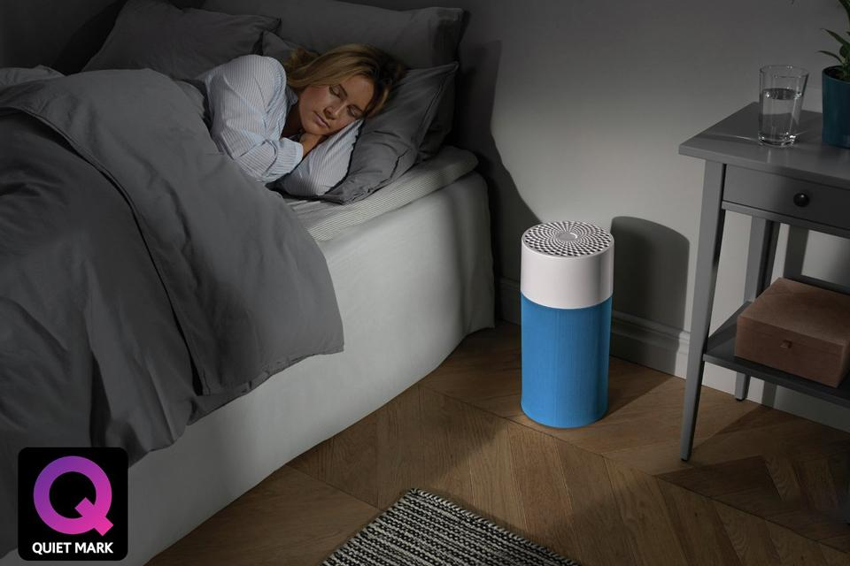 Woman sleeping beside a Blueair Blue Pure 411 Air Purifier.
