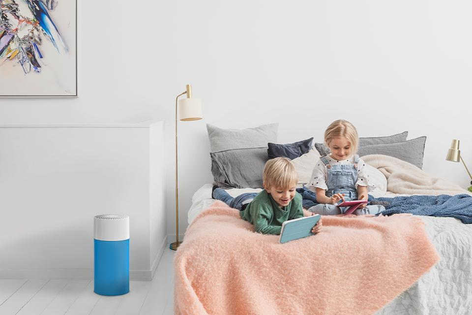 Two kids reading on a bed beside an air purifier.